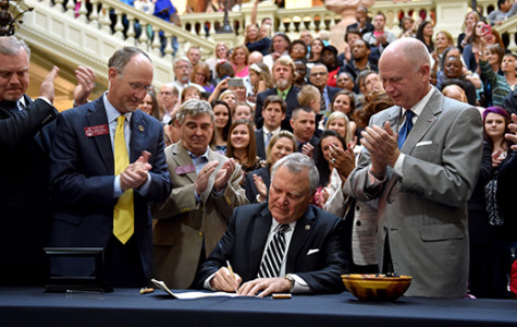 Governor Nathan Deal signs House Bill 1 into law surrounded by supporters of medical cannabis. He waited to sign the bill until the end of the legislative session to ensure its passing. Haleigh Cox was issued Georgia's first medical marijuana card at the signing.