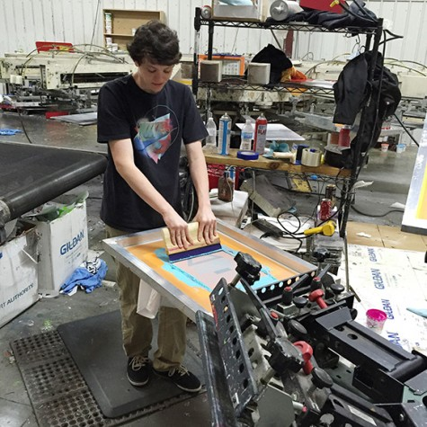 Sam Ozio uses a squeegee to push the ink onto a t-shirt. Ozio, Sam Bennett, Sam Jones and Ben Linkous-Stewart take pride in creating their own products.