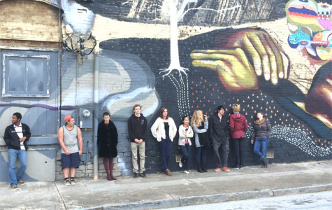 The students pose in front of A Living Walls mural near the Trinity Triangle.