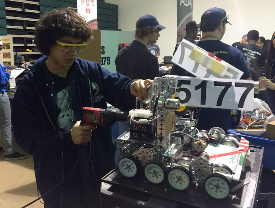Matthew Byars, Junior from 5177, adjusts a misdirected wire on the robot. Said wire is a part of a wench, a tool that extends and hoists the robot up inclines similar to a grappling hook.