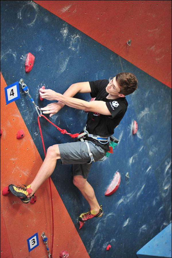 Ben Hammer clips his rope into his quickdraw in his first qualifying route at divisionals in June 2014 in Texas.