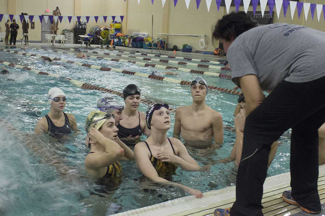 Swim coach Tania Kane gathers the team during warmups at the Agnes Scott College pool.