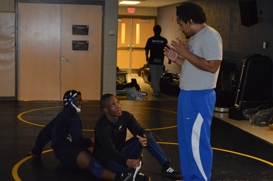 Coach Buggs shows Noah Boyer and Deaundre Wilson a new wrestling move that they plan to use in the sectional tournament.