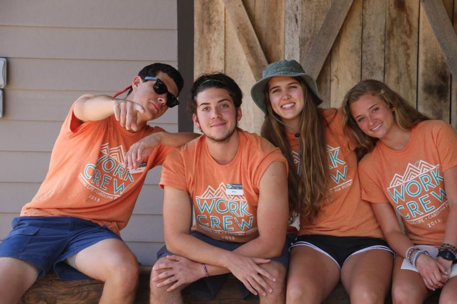 Clark Wilson, Max Kight, seniotr Olive McKay and Lauren Forster wait for the next bus of campers to arrive.  We cheer and shout and welcome the campers in, McKay said. Then we carry their bags to their cabins and tell them to have a great week.