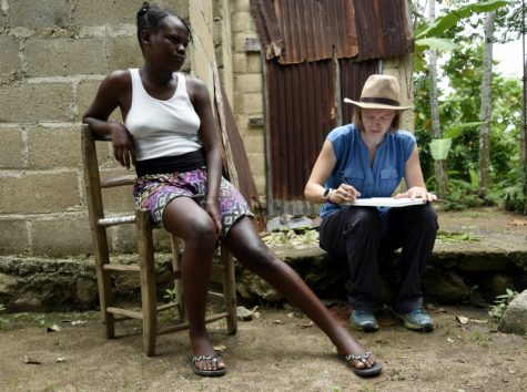 Task Force epidemiologist Katie Gass (right) confers with Dieulove Charles , a resident of Hati , about a potential lymphatic filariasis infection .