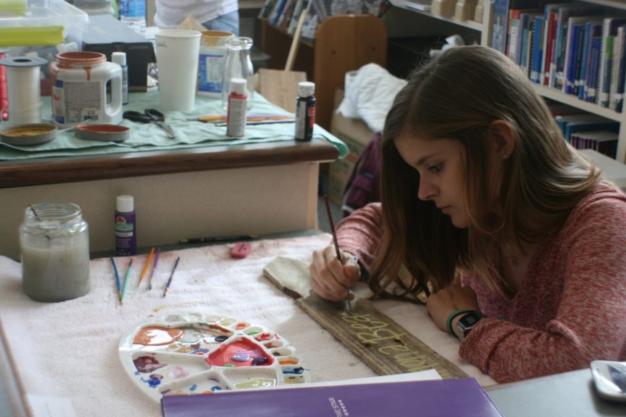 Sarah Grace Stafford paints destination signs in Clairemont's library to fulfill custom orders.