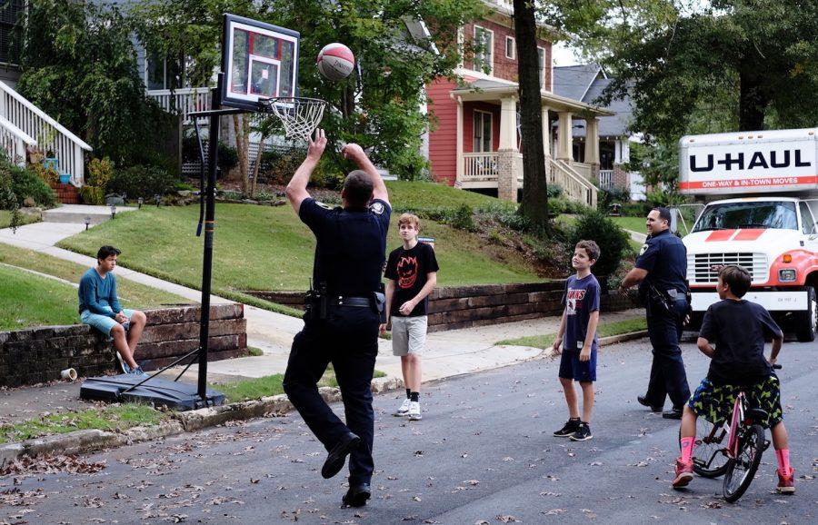 Officer Copeland and Officer Santiago play basketball with teenagers after the Madison Avenue Soapbox Derby. Photo courtesy of Jennifer Ross