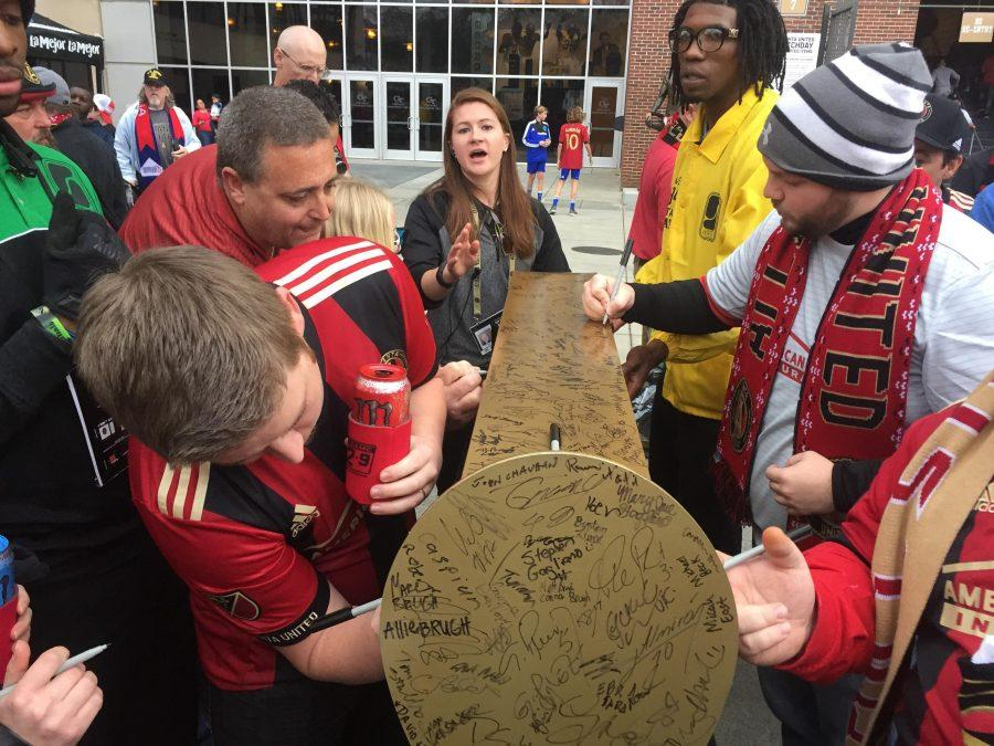 Fans+signed+the+golden+spike%2C+meant+as+a+symbol+of+Atlanta%27s+railroad+history%2C+before+the+game.+%28Photo+by+Graham+Cattanach%29