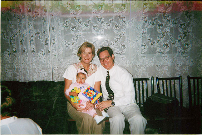 Valerie Vansweden (left) and Dave Quam (right), married at the time, hold one-year-old Eden (center) at a Russian orphanage. This was the very first moment her adoptive parents met her.