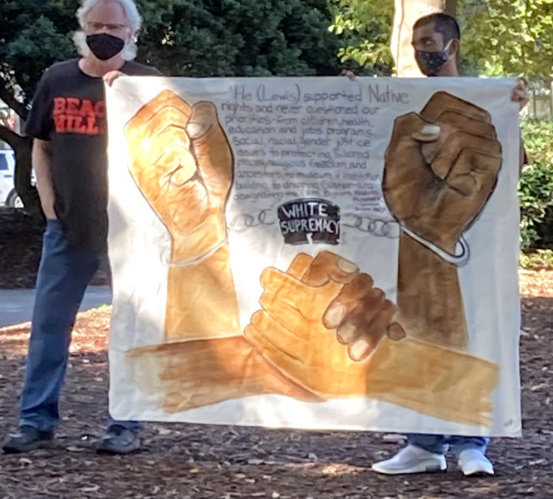 Decatur alum and Beacon Hill member Koan Roy-Meighoo (right) stands with a drawing made by a local Atlanta artist. The quote, written by Muscogee activist Susan Harjo, says: